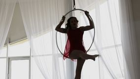 Aerial acrobat in the ring. A young girl performs the acrobatic elements in the air ring.  stock video