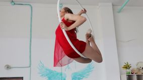 Aerial acrobat in the ring. A young girl performs the acrobatic elements in the air ring.  stock footage