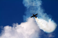 Aerial acrobatics plane in the cloud of smoke Stock Images