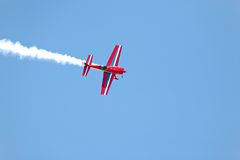 Aerial acrobatics stunt flying. Aerial acrobatics - red propeller plane with smoke trail against clear blue sky Royalty Free Stock Photography