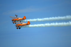 Aerial aerobatics Eastbourne Airshow UK. The unique Breitling Wingwalkers team perform a breathtaking sequence of acrobatic manoeuvres with women doing stunts on Royalty Free Stock Photos