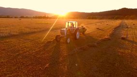 Aerial agricultural footage: tractor collecting hay and making haystacks. Haymaking during beautiful golden sunset. hd stock footage