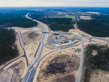 Aerial air view of a massive construction site with a heavy vehicle, bulldozer and excavator, building a new road, working and unl Royalty Free Stock Photo