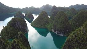 Aerial of Amazing Islands and Lagoon in Wayag, Raja Ampat. Rugged limestone islands, surrounded by coral reefs, are found in an idyllic, tropical lagoon in Wayag stock video footage