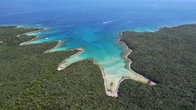 Aerial: amazing white sand beaches with clear blue water. Boat driving into bay stock video