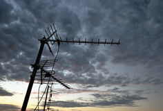 Aerial antenna on the roof with cloudy background. In the sunset Royalty Free Stock Image