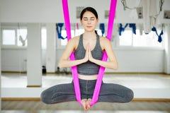 Aerial antigravity yoga girl in lotus pose on silk hammock Royalty Free Stock Photography