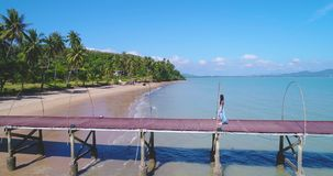 Aerial: An Asian girl walks on a pier towards the beach with palm trees. stock video