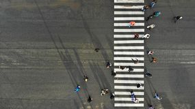 Aerial. Asphalt road with zebra pedestrian crosswalk and crowd of people. Top view.  stock images