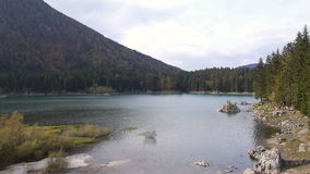 Aerial: autumn forest and peaceful lake in highlands. Tranquil landscape stock footage