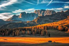 Aerial autumn sunrise scenery with yellow larches and small alpi. Ne building and Odle - Geisler mountain group on background. Alpe di Siusi Seiser Alm, Dolomite Royalty Free Stock Photography