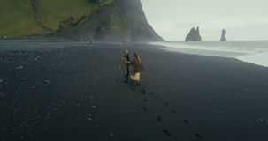 Aerial back view of the young hipster couple running on the black volcanic beach near the troll toes in Iceland. stock video footage