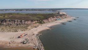 An aerial backward footage of the Hengistbury Head long Groyne restoration work scheme stock footage