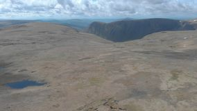 An aerial backward reveal footage of a Scottish summit plateau with huge cliff in the background stock video footage
