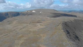 An aerial backward reveal footage of a Scottish summit plateau with huge cliff in the background 2 stock video