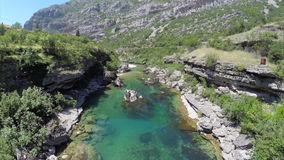 AERIAL: Beautiful blue mountain river running through sunny rocky valley. In Serbia stock footage
