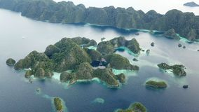Aerial of Beautiful, Limestone Islands in Raja Ampat. The stunning limestone islands found in Raja Ampat are surrounded by healthy coral reefs. This beautiful stock footage