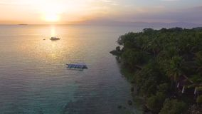 Aerial: Beautiful Tropical Beach Sunset With Wooden Boat In The Distance. Drone Shot Of Beautiful Sea Sunset LAndscape With Wooden Boat In The Distance In stock video footage
