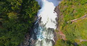 Beautiful water fall through forest cliff on a sunny day 4k. Aerial of beautiful water fall through forest cliff on a sunny day 4k stock video footage
