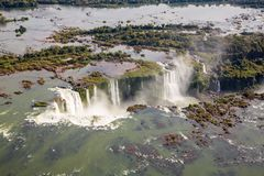 Aerial bird`s-eye view of beautiful rainbow above Iguazu Falls Devil`s Throat chasm from a helicopter flight. Brazil and Argentina royalty free stock photography