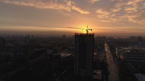 Aerial bird view of yellow tower building crane fly around construction site building apartments real estate from a. Helicopter cockpit view of houses homes stock video
