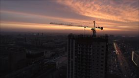 Aerial bird view of yellow tower building crane fly around construction site building apartments real estate from a. Helicopter cockpit view of houses homes stock video footage