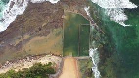 Aerial birds eye drone shot of an ocean rock pool near Sydney, Australia. Aerial birds eye drone shot of an ocean rock pool on the beach with swimmers near stock video