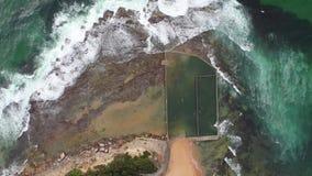 Aerial birds eye drone shot of an ocean rock pool near Sydney, Australia. Aerial birds eye drone shot of an ocean rock pool on the beach with swimmers near stock video footage