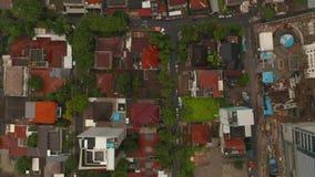 Aerial birds eye overhead top down view moving along the street in dense urban neighborhood in Jakarta, Indonesia