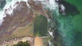 Aerial birds eye shot of an ocean rock pool near Sydney, Australia. Aerial birds eye drone shot of an ocean rock pool on the beach with swimmers near Sydney, NSW stock footage