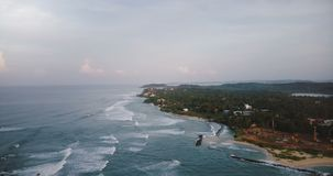 Aerial birds eye view of beautiful foaming sea waves breaking near tropical shore with green trees and construction site. Drone flying high above peaceful sea stock video