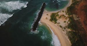 Aerial birds eye view of beautiful foaming sea waves reaching shore, stone breakwater and coastline construction site. Drone flying over peaceful summer stock footage