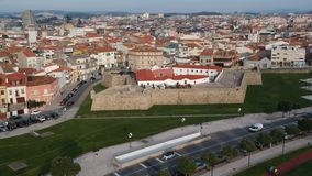 Aerial birds eye view of city of Povoa de Varzim in Portugal, flying slowly forwards. With old Napoleonic fort in foreground stock video footage