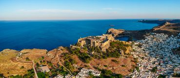 Aerial birds eye view drone photo of village Lindos, Rhodes island, Dodecanese, Greece. Sunset panorama with castle, Mediterranean. Sea royalty free stock photography