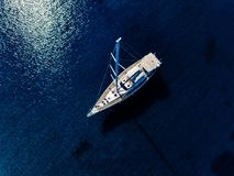 Aerial birds eye view from drone of yacht in deep blue sea stock photos