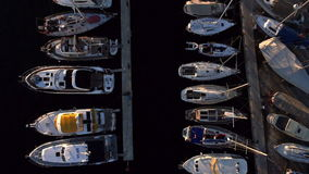 Aerial: birds view of marina docks with boats docked and sailing boats at sunset stock video footage
