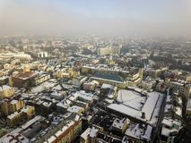 Aerial black and white winter top view of modern city center with tall buildings and parked cars on snowy streets.  stock photo