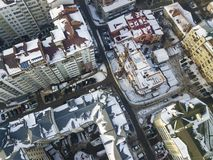Aerial black and white winter top view of modern city center with tall buildings and parked cars on snowy streets.  stock photography