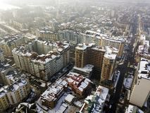 Aerial black and white winter top view of modern city center with tall buildings and parked cars on snowy streets.  royalty free stock photography