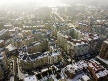 Aerial black and white winter top view of modern city center with tall buildings and parked cars on snowy streets.  stock photos