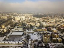 Aerial black and white winter top view of modern city center with tall buildings and parked cars on snowy streets.  royalty free stock images