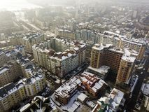 Aerial black and white winter top view of modern city center with tall buildings and parked cars on snowy streets.  royalty free stock image