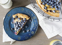 Aerial of blueberry tart on blue plate, on tabletop with napkin. Stock Photo
