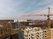 Aerial of a building site with a large operating bright yellow crane near a house royalty free stock images