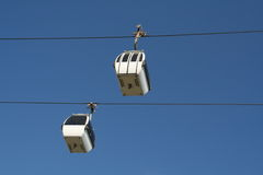 Aerial cable cars. Low angle view of two modern aerial cable cars with blue sky background Stock Images