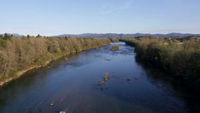AERIAL: Calm river with trees beside the river bed in autumn at sunset stock video footage