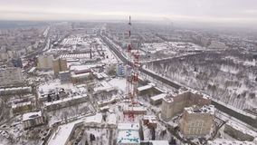 Aerial camera is approaching to a tv tower in daytime in winter. Cityscape is in background stock footage