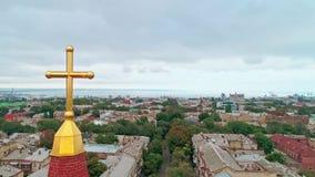 Aerial camera moving upwards revealing Christian Religious Cross over the city of Odessa. Religion concept.