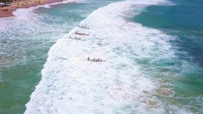 Drone footage of an ocean rowing competition in Sydney, Australia. Aerial capture of a traditional rowing teams entering the sea over waves/surf and competing in stock footage