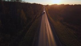 Aerial: the car with the container rides on the road to the sunset. Truck rides the highway. Aerial: the car with the container rides on the road to the sunset stock footage
